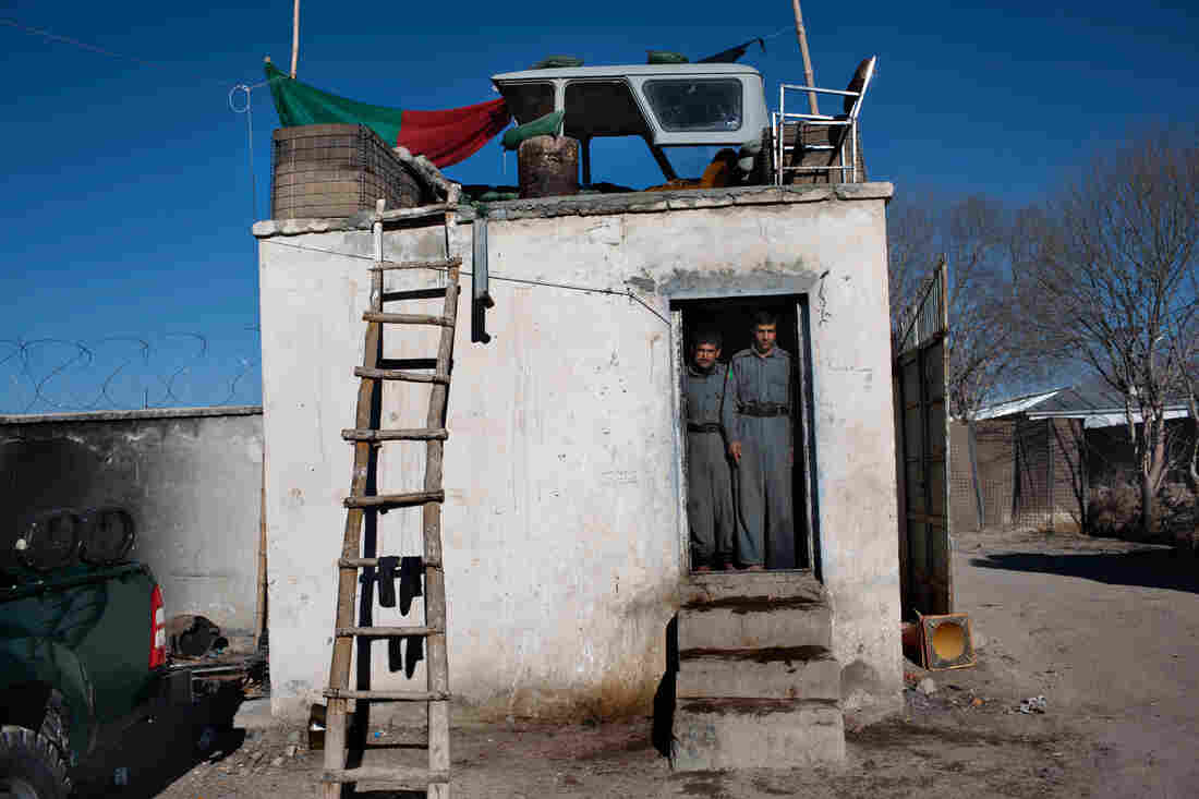 Two Afghan National Police officers stand at a guard post at a district center in Ghazni province in 2009.