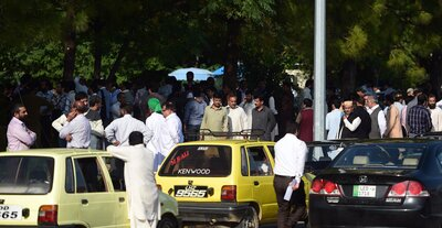 Pakistani federal employees gather outside their offices after a 7.5-magnitude earthquake in Islamabad on Monday. (Farooq Naeem/AFP/Getty Images)