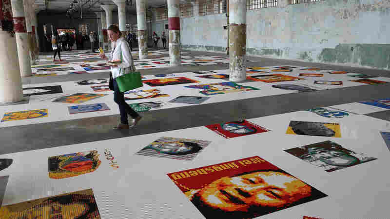 """Visitors look at Ai Weiwei's """"Trace"""" installation — part of the @Large: Ai Weiwei on Alcatraz series — last year on Alcatraz Island in the San Francisco Bay."""