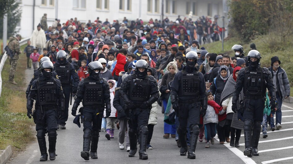 Migrants walk toward Austria from a camp in Sentilj, Slovenia, on Sunday. Many migrants are from Syria and are sometimes from opposite sides of the country's war. (Petr David Josek/AP)