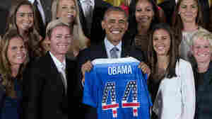 President Obama poses with a jersey he received from the U.S. Women's National Soccer Team during a ceremony to honor the team and their victory in the 2015 FIFA Women's World Cup. Standing with Obama are (from left) Christie Rampone, Morgan Brian, Abby Wambach, Julie Johnston, Sydney Leroux, Carli Lloyd, Alex Morgan, and Megan Rapinoe.