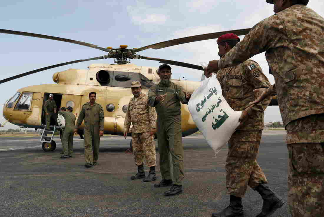 Army soldiers load sacks of food aid on a helicopter to distribute in earthquake-stricken areas in Peshawar, Pakistan, on Tuesday.