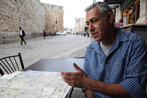 Ami Meitav, a former Israeli intelligence officer and now a tour guide, looks at a map of Jerusalem's Old City as he sits near one of the entrances. He would like to see cameras at the religious site, but believes Muslim religious authorities will oppose the plan.