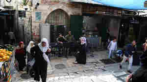 Palestinian shoppers walk near Damascus Gate in Jerusalem's Old City, under the watchful eye of Israeli police and wall-mounted security cameras. Amid the recent violence, there's talk of placing cameras inside the city's most contested religious site, known as the Temple Mount to Jews and the Al-Aqsa mosque compound to Muslims.