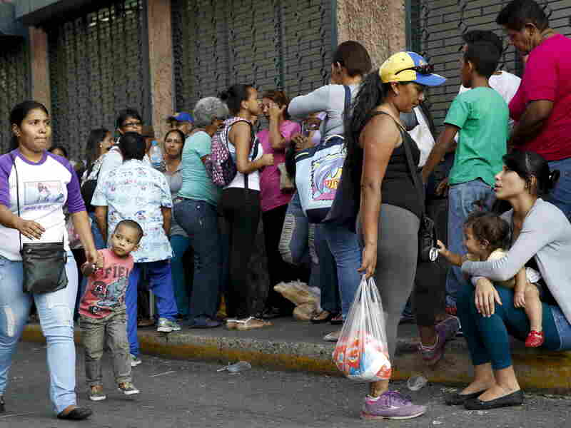 Mothers take care of their children while lining up to buy staple goods outside a supermarket in Caracas earlier this month.