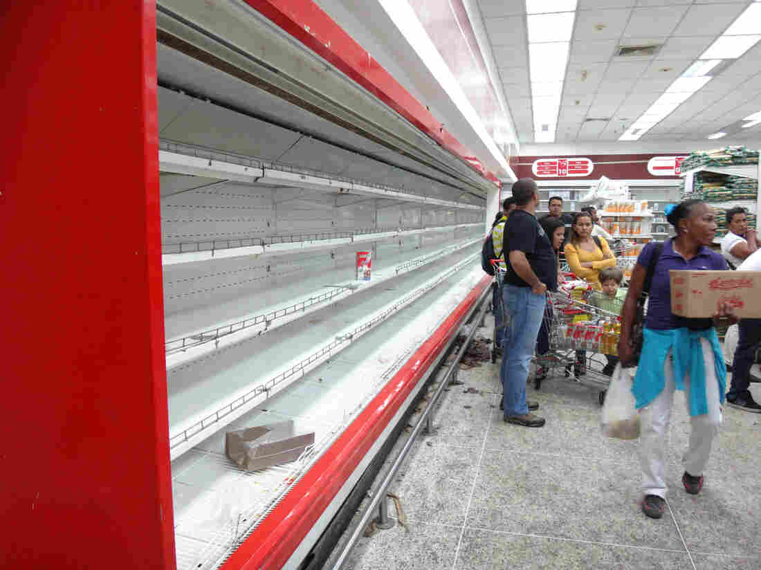 Empty shelves, like these at a supermarket in Caracas, are a common sight in Venezuela. People can shop only on designated days at government-run stores. They're limited in what they can buy and must undergo fingerprint scanning to prove their identity.