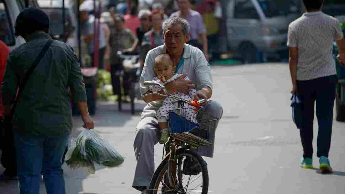 Faced with an aging population, China has eased its one-child policy. Here, an elderly man is seen holding a baby as he rides a bicycle in Beijing last month.