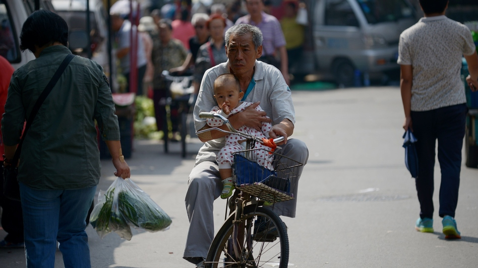Faced with an aging population, China has eased its one-child policy. Here, an elderly man is seen holding a baby as he rides a bicycle in Beijing last month. (Wang Zhao/AFP/Getty Images)