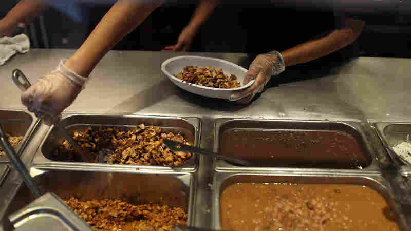 Chipotle restaurant workers fill orders for customers. The company is now sourcing some of its pork from a British supplier that uses antibiotics to treat pigs when ill. Gail Hansen, a veterinarian and longtime critic of antibiotic overuse on farms, welcomes this shift in Chipotle's stance on the drugs.