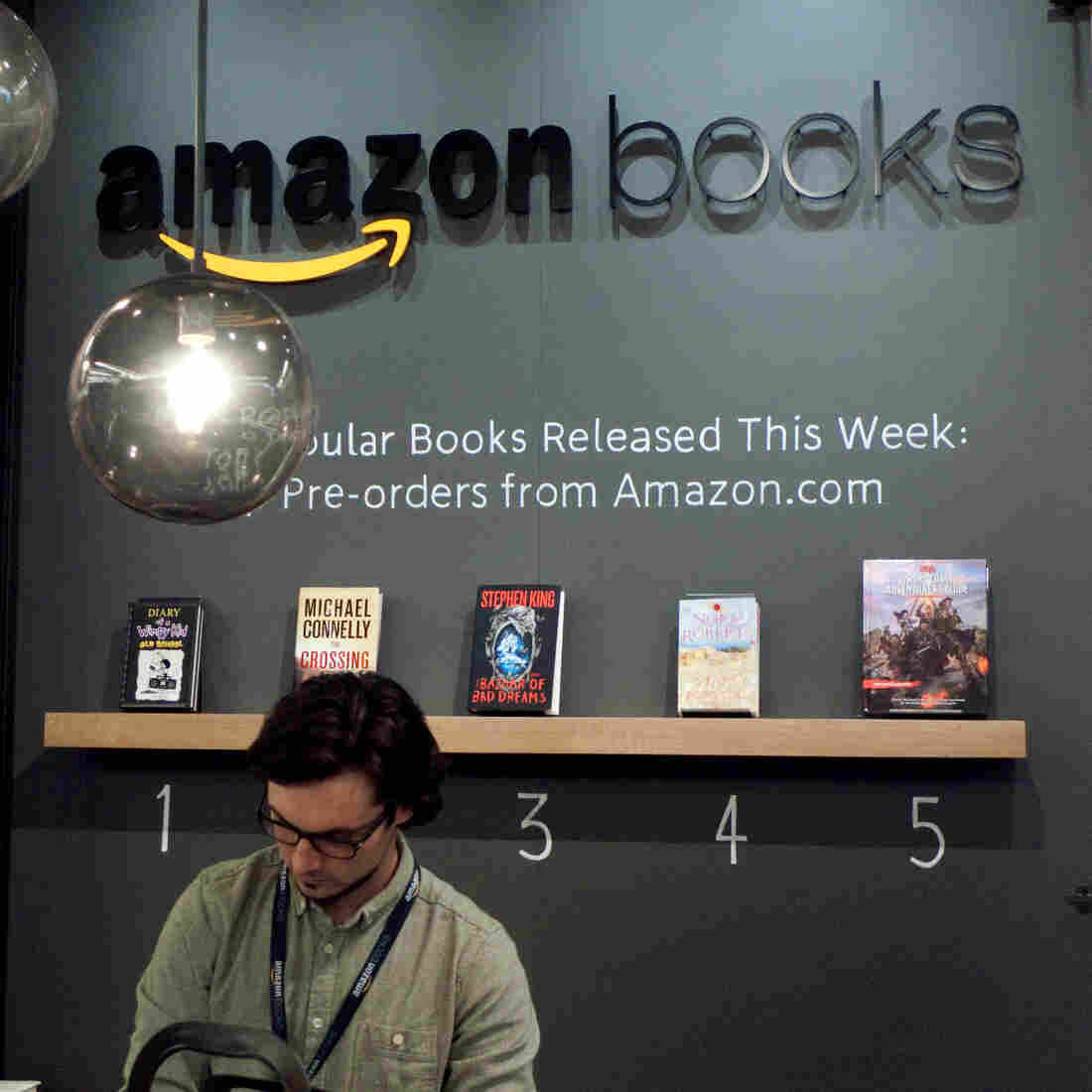 A clerk works the counter at Amazon Books, the retailer's first brick-and-mortar store that opened in Seattle Tuesday.