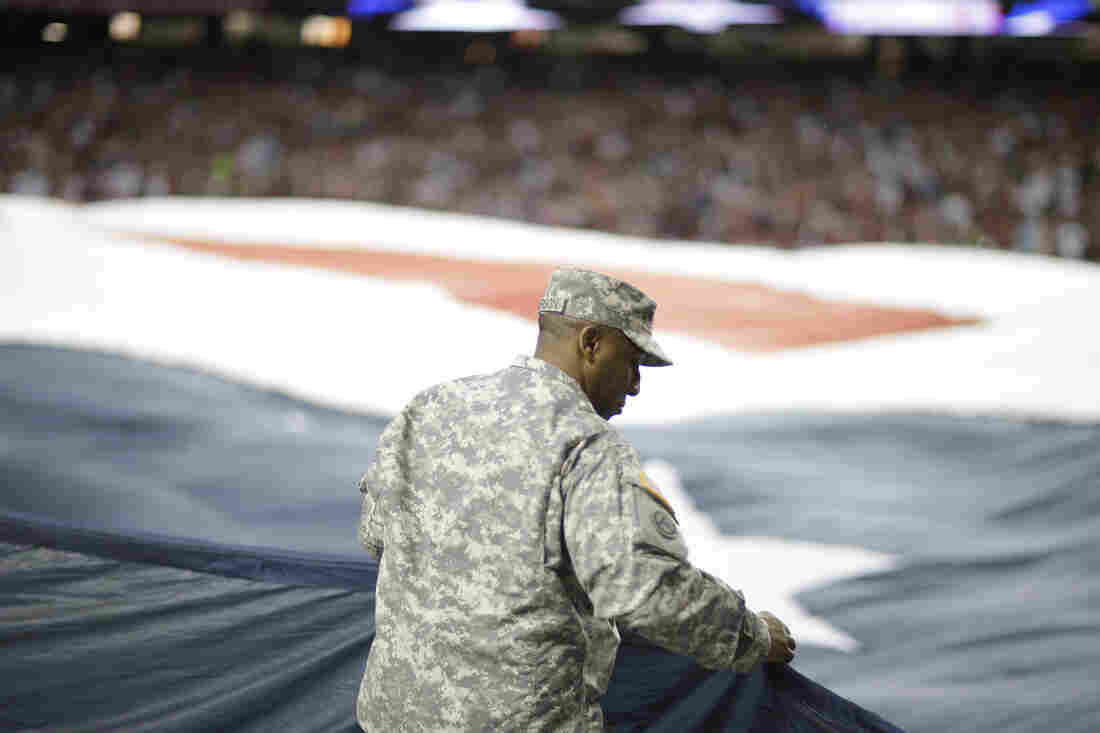 Paid advertisement? A soldier holds an American flag before the first half of a 2013 NFL football game between the Atlanta Falcons and the New England Patriots in Atlanta.