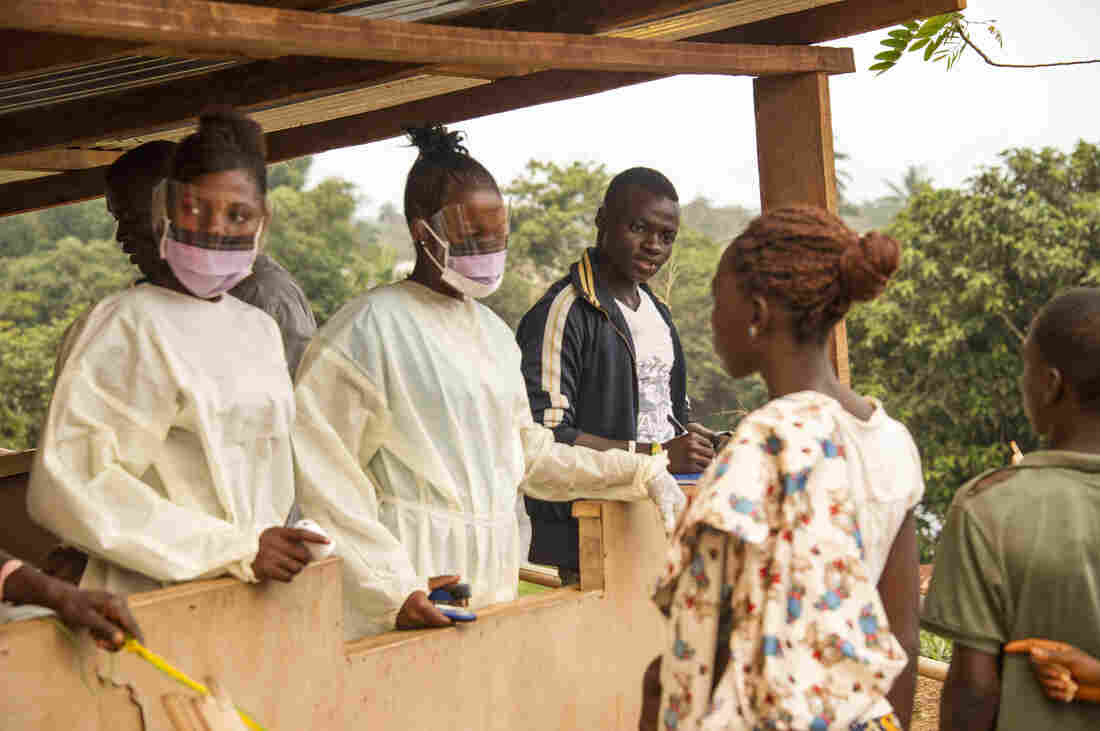 Health workers in Sierra Leone check travelers entering the country from Liberia.
