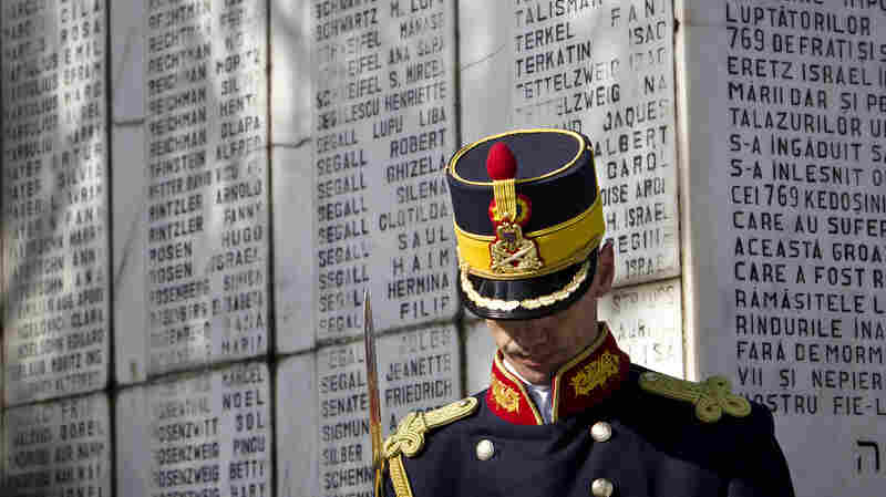 An honor guard soldier stands next to a monument in Bucharest, Romania, in Feb. 2012, that bears the names of Jews killed when the SS Struma — the ship they were on as refugees on their way to what was then Palestine — was sunk by a Soviet torpedo in the Black Sea. All but one of the 779 people on board died.