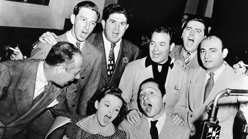 Composer Harold Arlen (sitting, right) joins Judy Garland, Bert Lahr (far left), Ray Bolger (back row, left) and various executives for a Wizard of Oz sing-along in the NBC radio studio, circa 1939. (Getty Images)