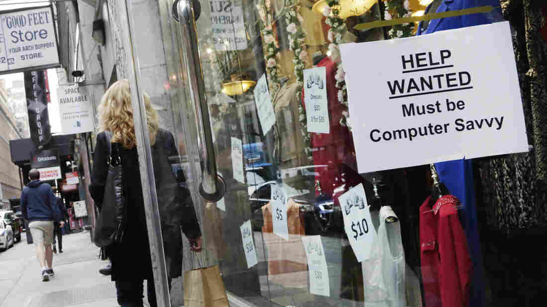 """A shopper walks past a store with a """"Help Wanted"""" sign last month in New York. The Bureau of Labor Statistics reported a 9-cent rise in the average hourly earning rate for October."""