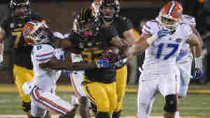 In this photo from Oct. 10, Missouri running back Russell Hansbrough (center) fights his way past Florida's Nick Washington (left) and Jordan Sherit during an NCAA college football game in Columbia, Mo. Some Missouri football players announced Saturday night on Twitter that they would not participate in team activities until the university president, Tim Wolfe, is removed from office.