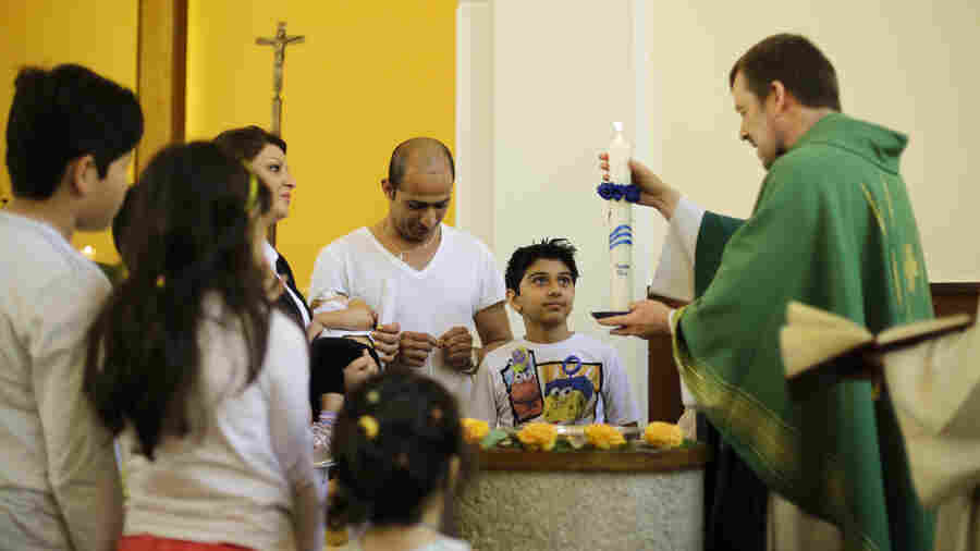 In Berlin, the Rev. Gottfried Martens lights a candle during a service to baptize Iranians in the Trinity Church. Iranian and Afghan converts make up most of the 900-member congregation.