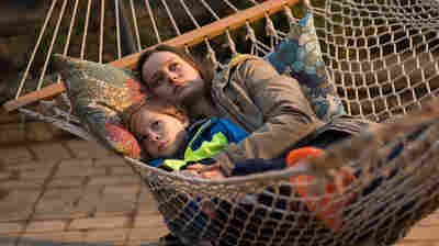 Ma (Brie Larson) snuggles with her son Jack (Jacob Tremblay) in Room.