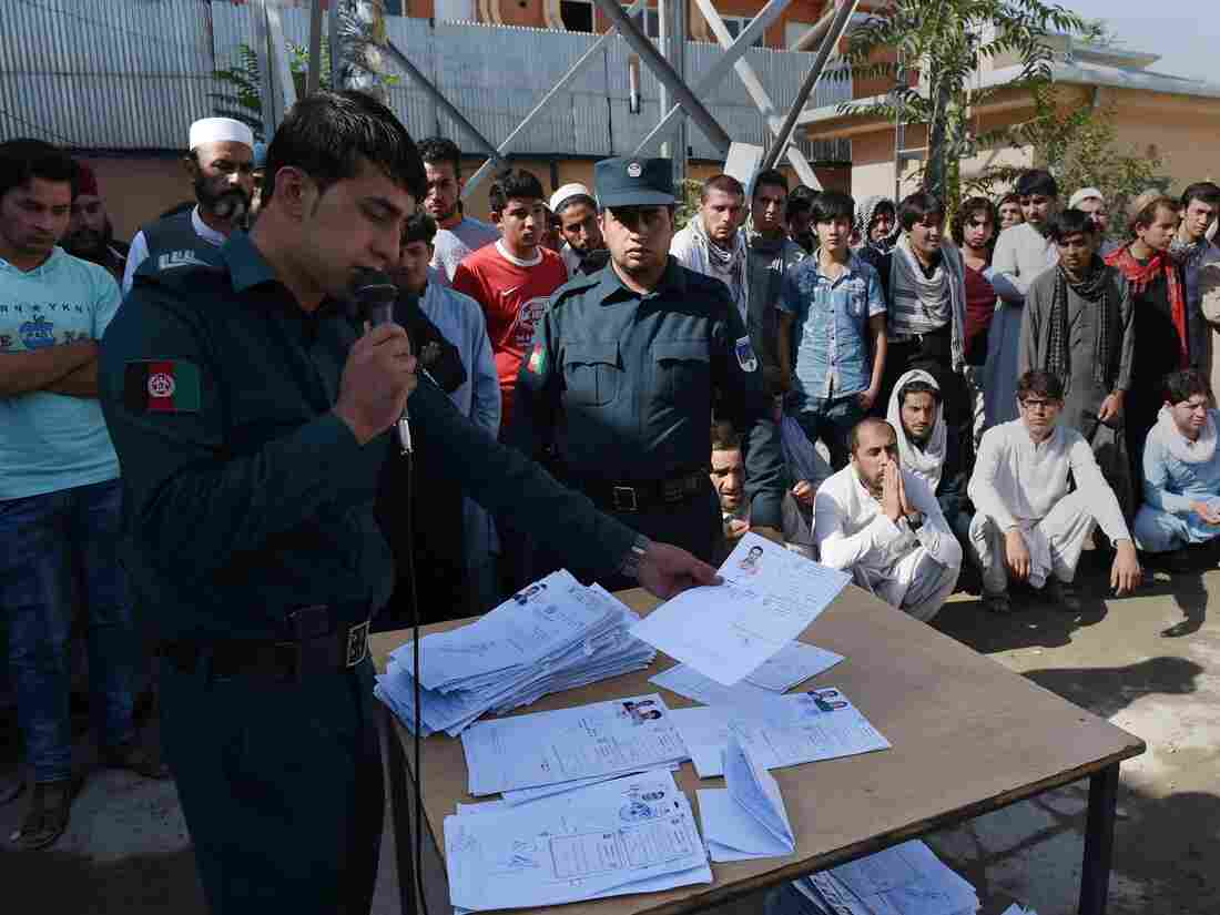 As worries grow over unemployment and lack of security, many Afghans are trying to go elsewhere. An Afghan National Police officer calls out the names of passport applicants at the passport office in Kabul in August.