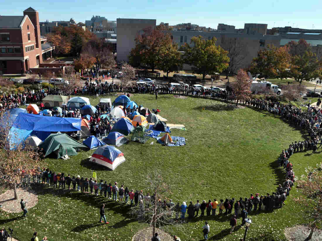 University of Missouri students circle tents on the Carnahan Quadrangle, locking arms to prevent media from entering the space following the resignation of President Timothy Wolfe on Monday.