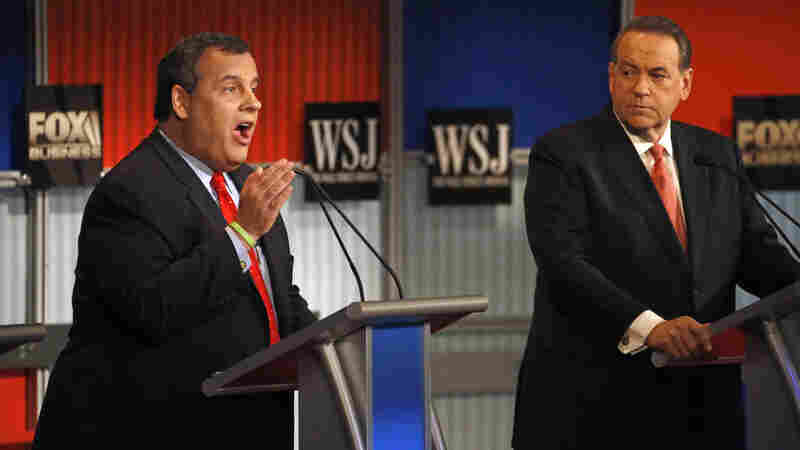 Chris Christie, left, makes a point as Mike Huckabee listens during Republican presidential debate in Milwaukee, Wis., on Tuesday.