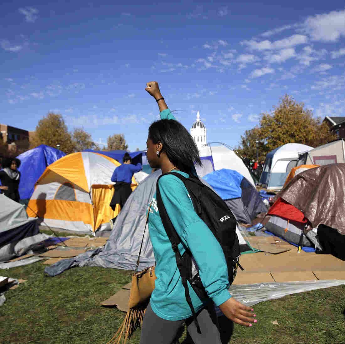 A woman passes a tent encampment set up by student protesters at the University of Missouri in Columbia.
