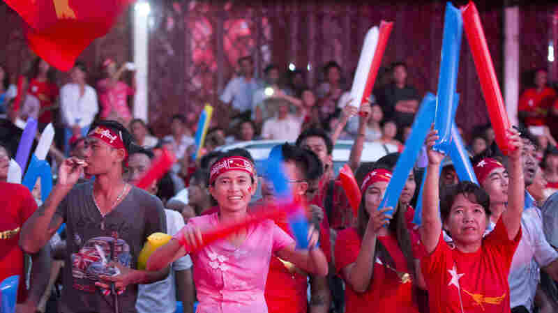 Supporters of Myanmar's National League for Democracy cheer as election results are posted outside party headquarters in Yangon, Myanmar's capital. Aung San Suu Kyi and other opposition leaders have tried to temper the celebrations, in anticipation of having to form a coalition — and contend with the military.