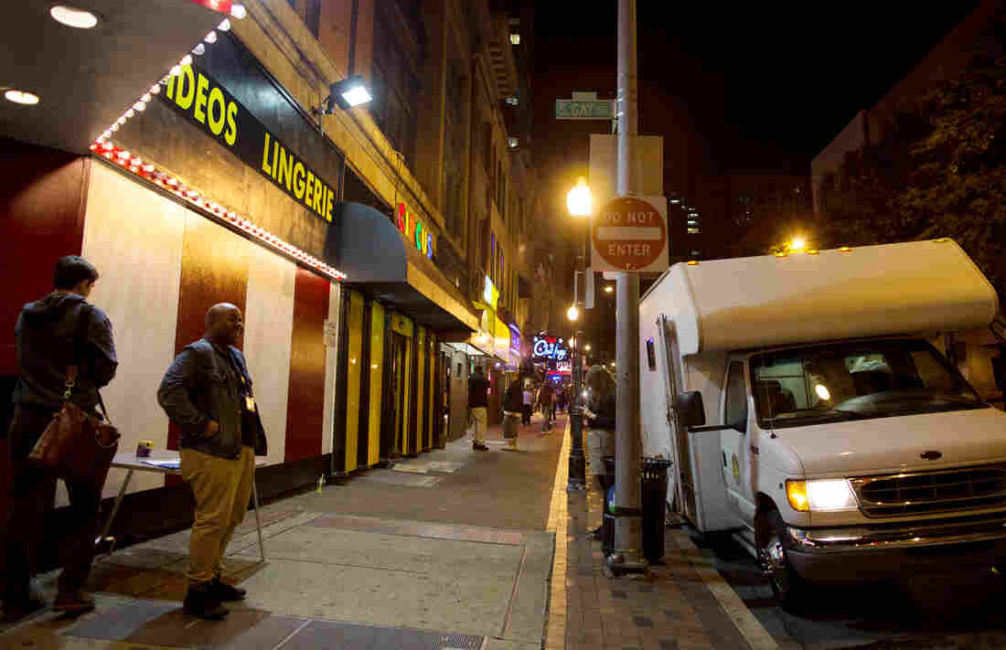 The needle exchange van parks on the corner of a block that is home to numerous strip clubs.