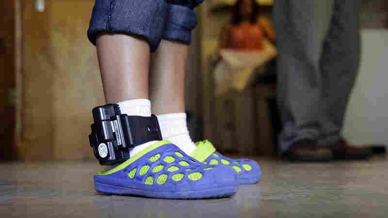 An adult immigrant from El Salvador who entered the country illegally wears an ankle monitor July 27 at a shelter in San Antonio. Lawyers representing immigrant mothers held in a South Texas detention center say the women have been denied counsel and coerced into accepting ankle-monitoring bracelets as a condition of release, even after judges made clear that paying their bonds would suffice.