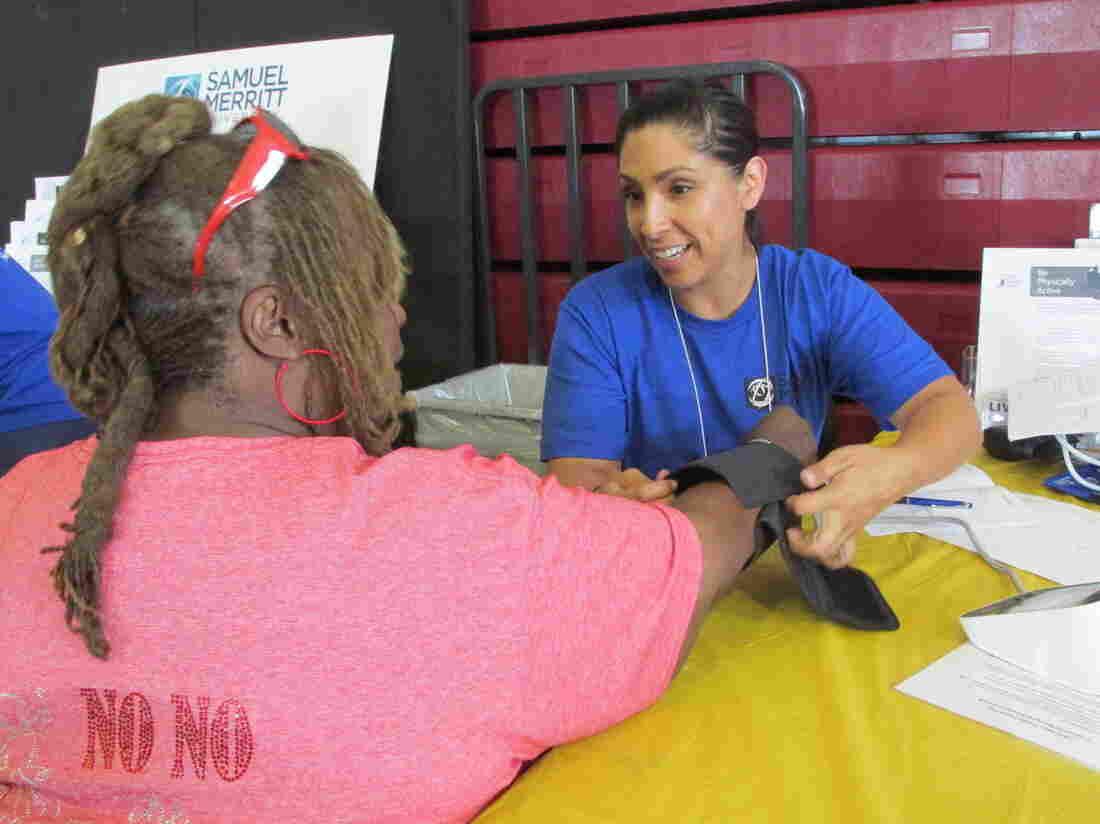 Diana Venegas, a nursing student at Samuel Merritt University, in Oakland, Calif., takes a patient's blood pressure at a recent health fair at Allen Temple Baptist Church.