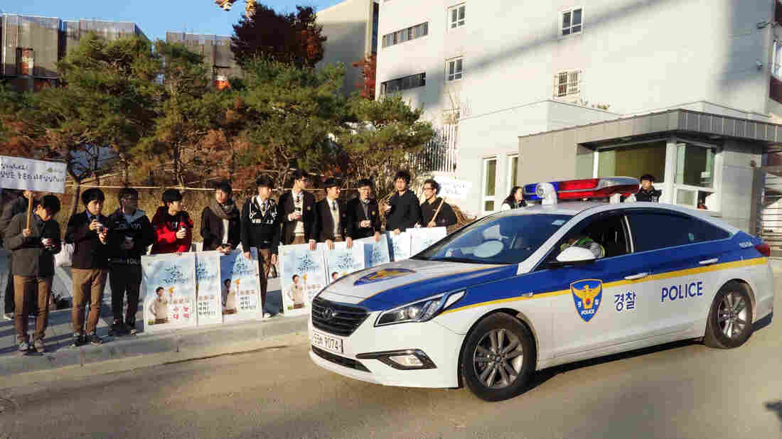 Younger students cheer on high school seniors as they head to the all-important college entrance exam on Thursday. As usual, police offered escorts for students who were running late.