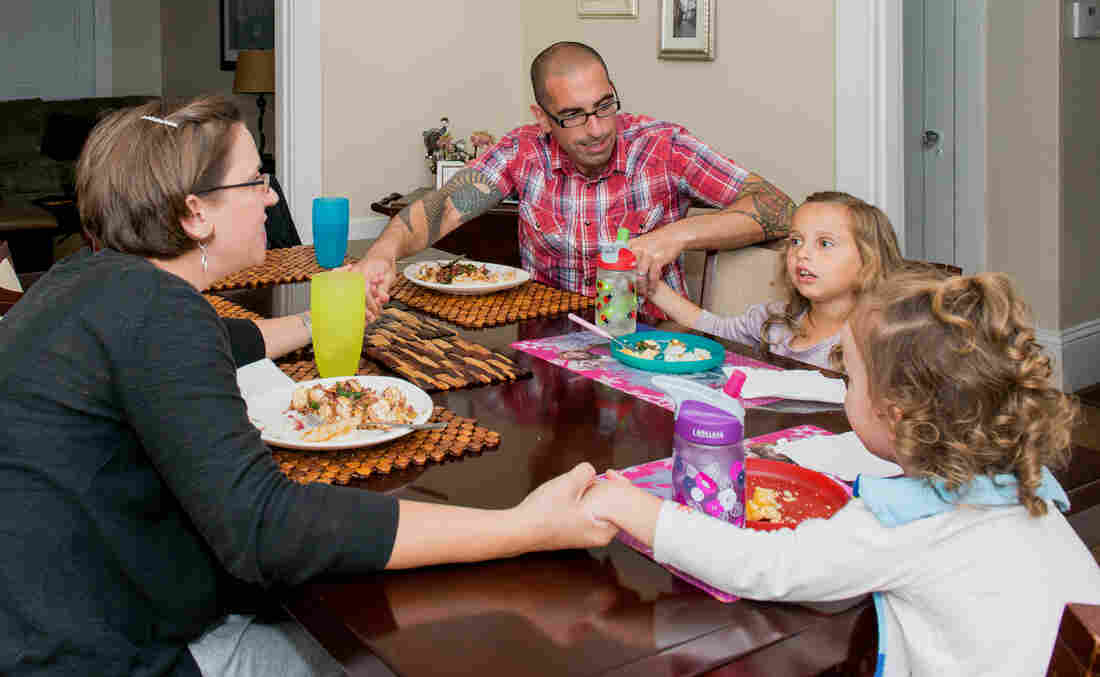 Anne Shamiyeh says grace before a meal with her husband, Omar Shamiyeh, and their two daughters, Zara and Malia. Anne says faith played a strong role in helping the family deal with the death of Malia's twin brother, Kai, in 2013.