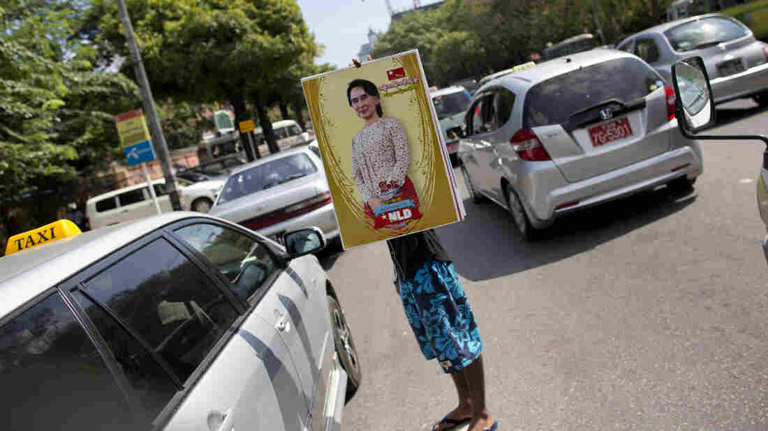 A vendor holds a calendar featuring Myanmar's opposition leader Aung San Suu Kyi in Myanmar. Myanmar's current president has promised a peaceful transfer of power.