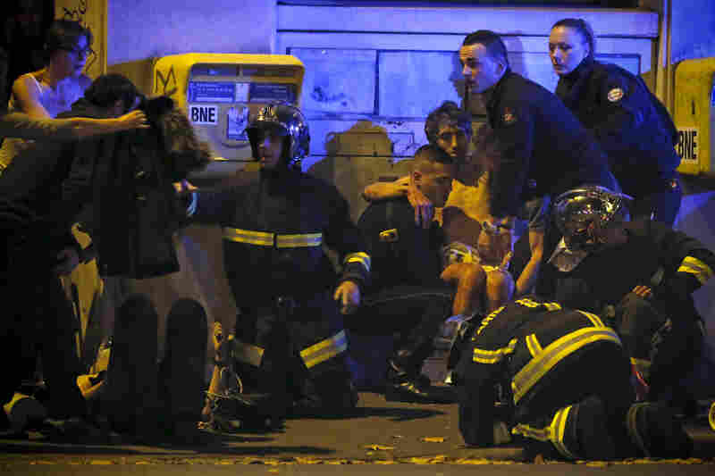 French fire brigade members aid an injured individual near the Bataclan following the shootings.
