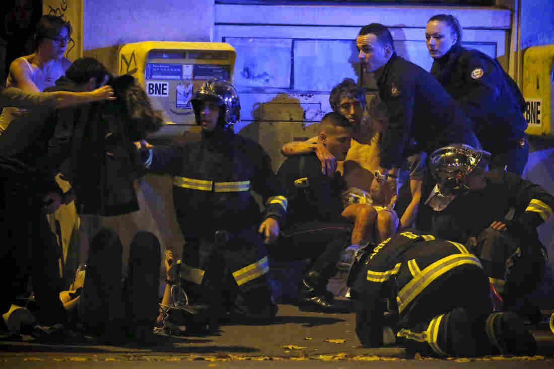 French fire brigade members aid an injured person near the Bataclan concert hall.