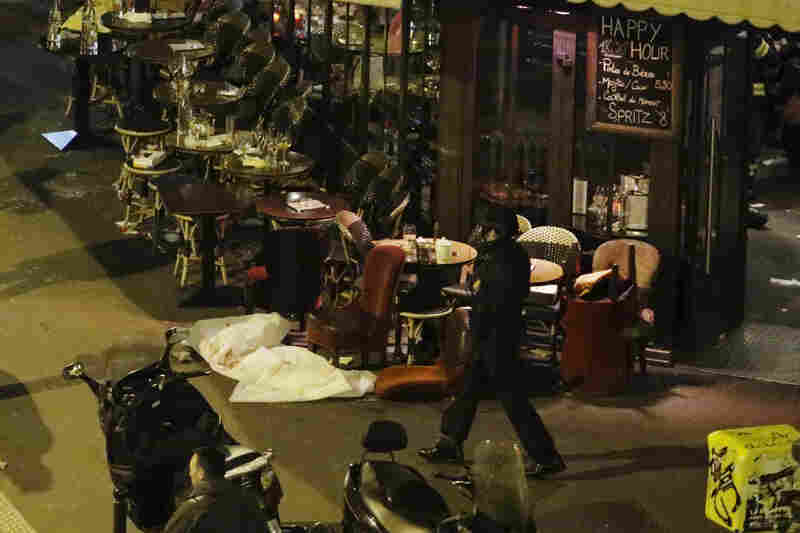 A white sheet covers a victim on the ground outside a restaurant in central Paris.