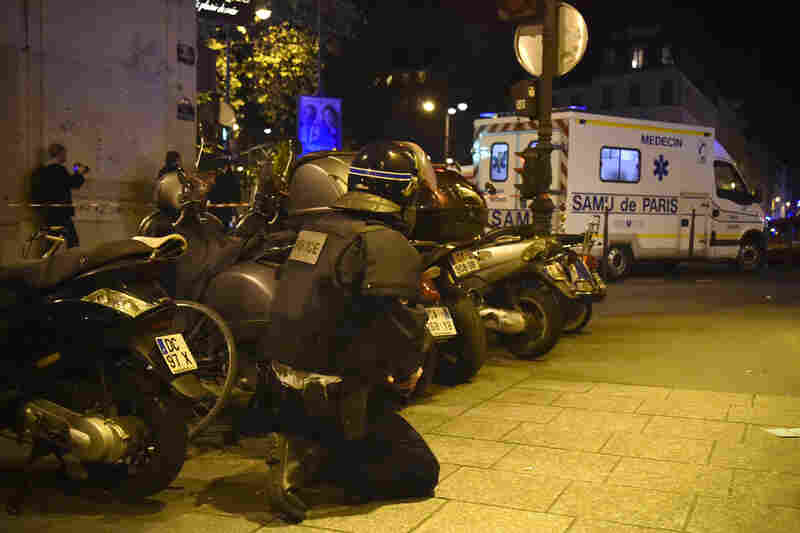 A riot police officer stands by an ambulance near the Bataclan.