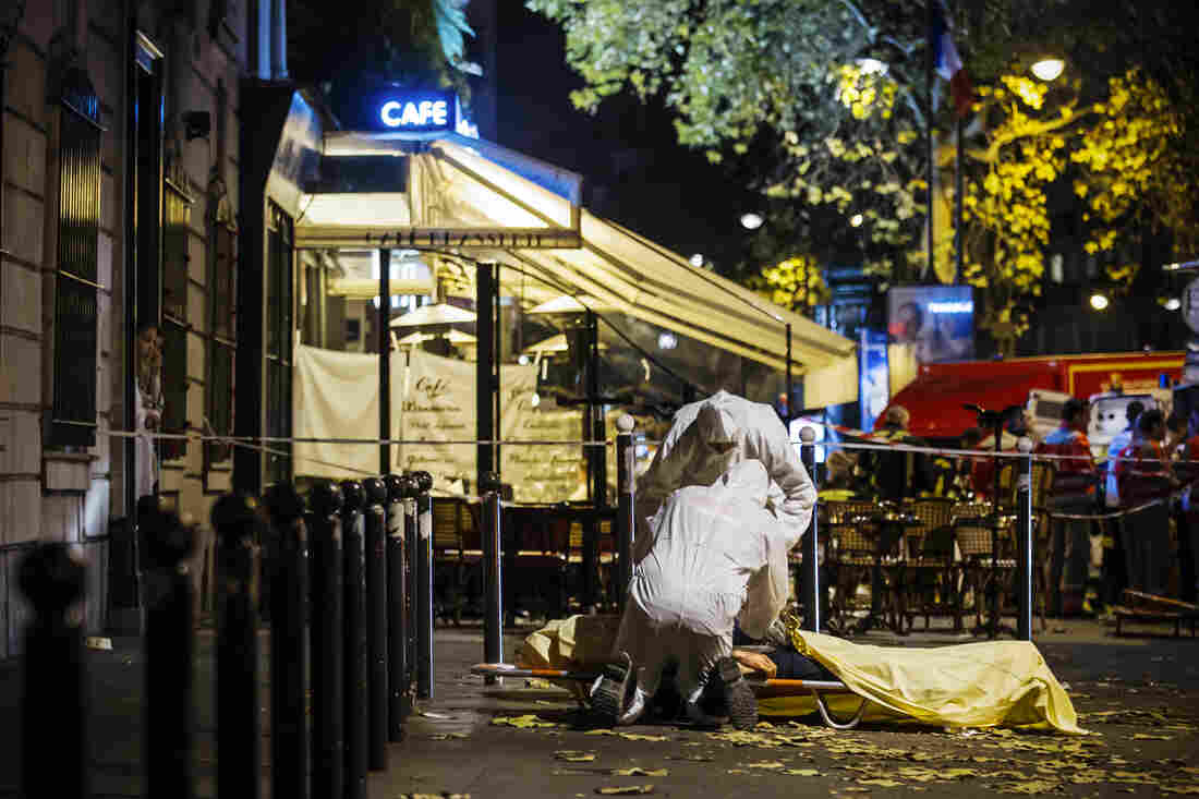 Investigators inspect the body of a victim outside the Bataclan concert hall.