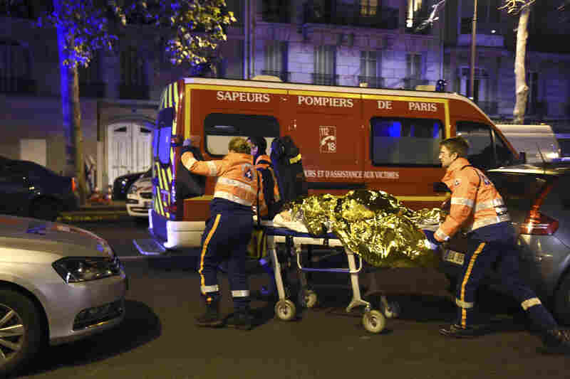 Rescue workers evacuate an injured person on Boulevard des Filles du Calvaire, near the Bataclan.