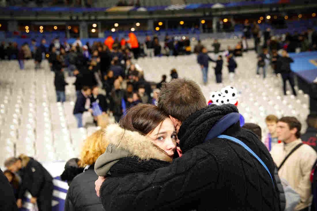 Spectators embrace on the playing field of the Stade de France after explosions were heard nearby. France and Germany had played a friendly match at the stadium in Saint Denis, outside Paris.