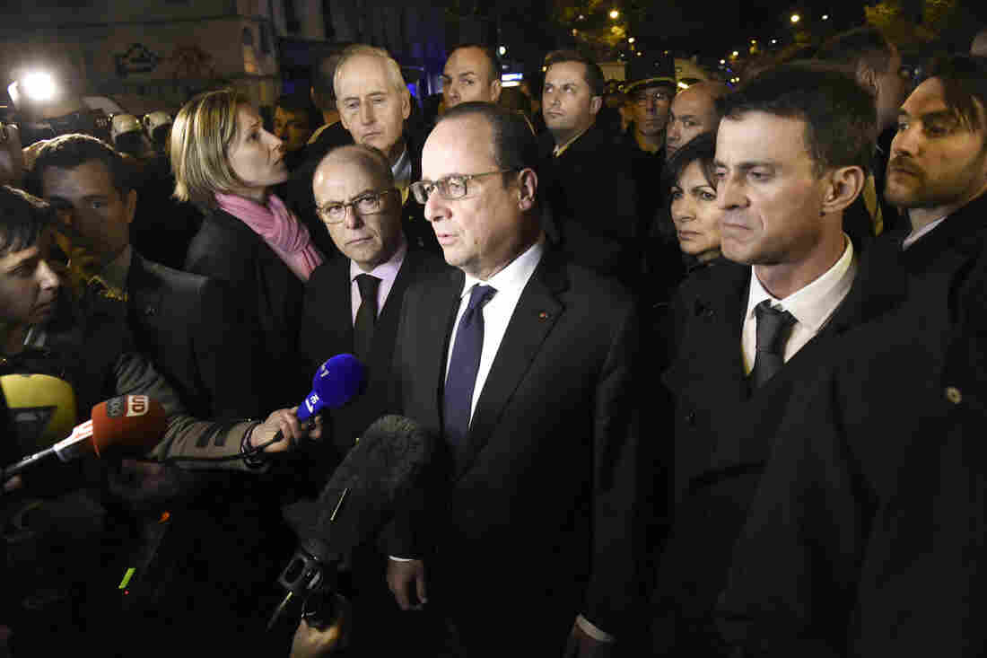 French President Francois Hollande (center), flanked by French Interior Minister Bernard Cazeneuve (left) and French Prime Minister Manuel Valls (right), addresses reporters near the Bataclan.
