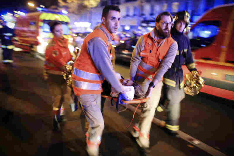 People wearing survival blankets walk by a rescuer near the Bataclan concert hall in central Paris. A French police official is quoted by the Associated Press as saying at least 100 people were killed inside the concert hall.