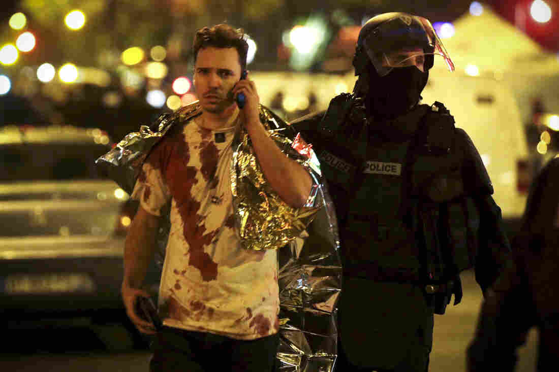 A French policeman assists a victim near the Bataclan concert hall.