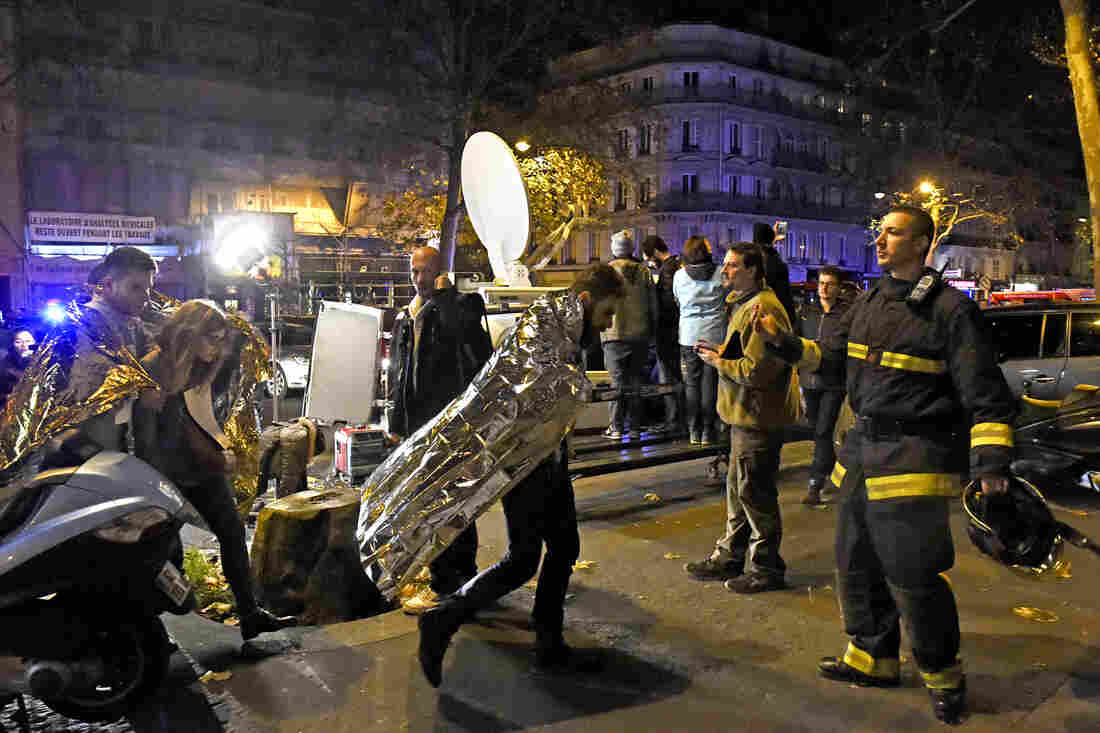 People wearing survival blankets walk by a rescuer near the Bataclan concert hall.