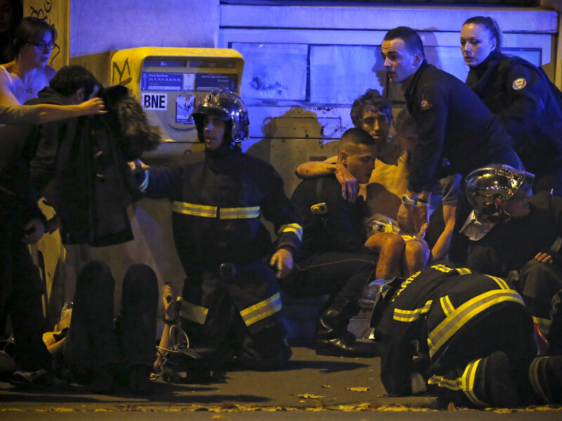 French fire brigade members aid an injured individual near the Bataclan concert hall following fatal shootings in Paris, France.