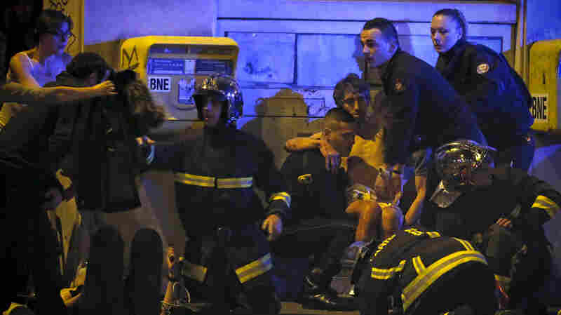 French fire brigade members aid an injured individual near the Bataclan concert hall following fatal shootings in Paris.