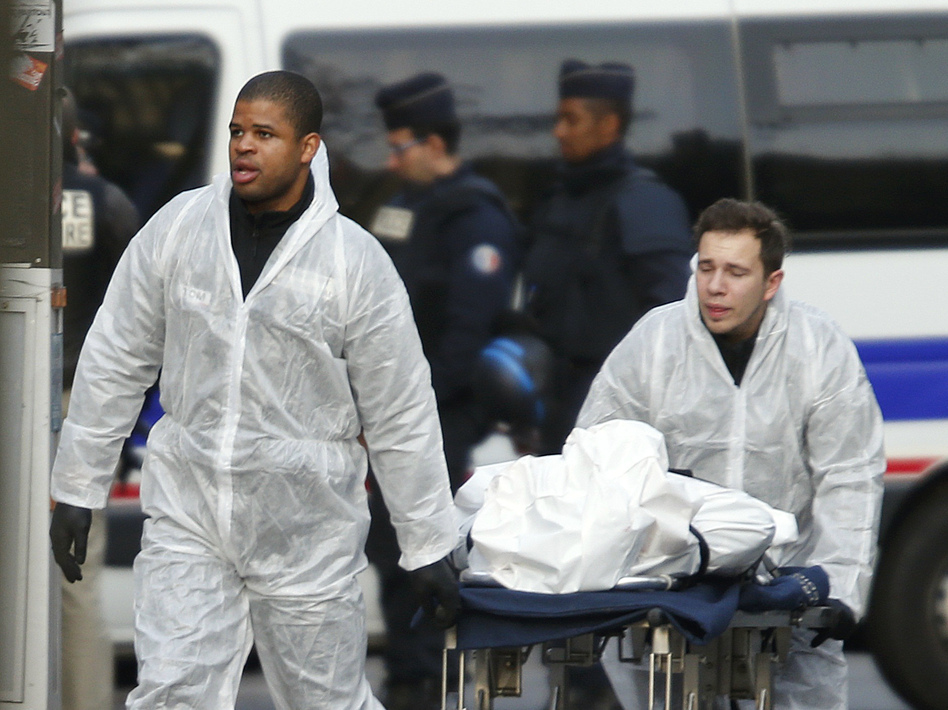 A victim is wheeled out of the Bataclan concert hall Saturday morning after a series of deadly attacks in Paris. (Charles Platiau/Reuters/Landov)