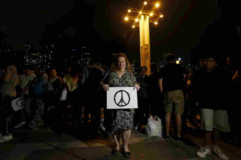 A mourner holds a Peace for Paris poster during a vigil in Hong Kong on Saturday for the victims of the Paris attacks.