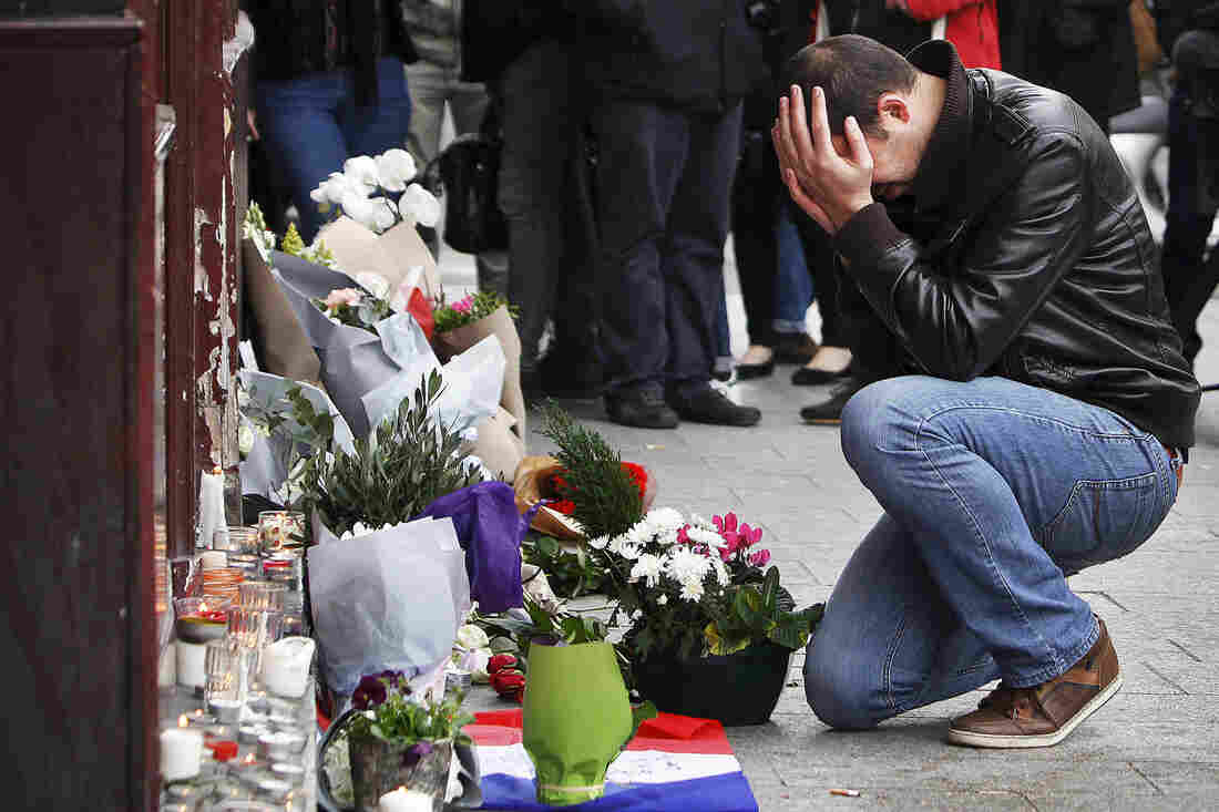 A man holds his head in his hands as he leaves flowers in front of the Carillon cafe on Saturday morning.