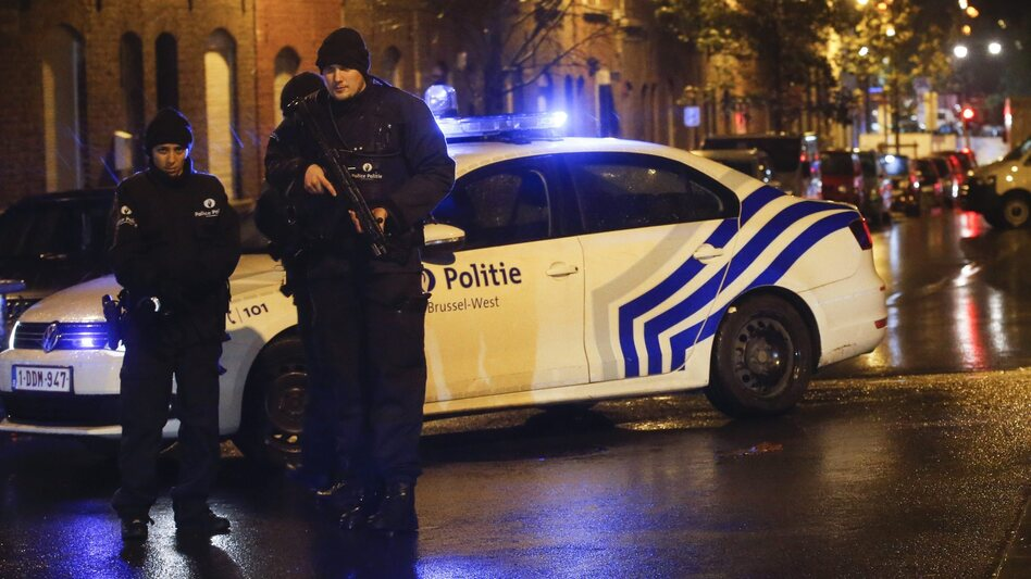 Police officers investigate the scene in the streets of Molenbeek, Brussels, Belgium, on Saturday. Officials say a man has been arrested in in connection with the terrorist attacks in Paris. (Olivier Hoslet /Landov)